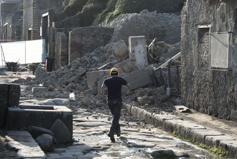 A worker jumps over a puddle among debris in the ancient Roman city of Pompeii, Italy, Saturday, Nov. 6, 2010. Officials say that a house in the ancient Roman city of Pompeii once used by gladiators to train before combat has collapsed. The site was closed at the time and nobody was injured. The office of Pompeii's archaeological superintendent said the collapse occurred Saturday at around 6 a.m. (0500 GMT). Attendants opening the site saw the collapse about an hour later. The 430-square-foot (40-square-meter) space was used by gladiators to train before going to fight in a nearby amphitheater. Pompeii was destroyed in A.D. 79 by an eruption of Mount Vesuvius that killed thousands of people and buried the city in 20 feet (six meters) of volcanic ash. (AP Photo/Salvatore Laporta)