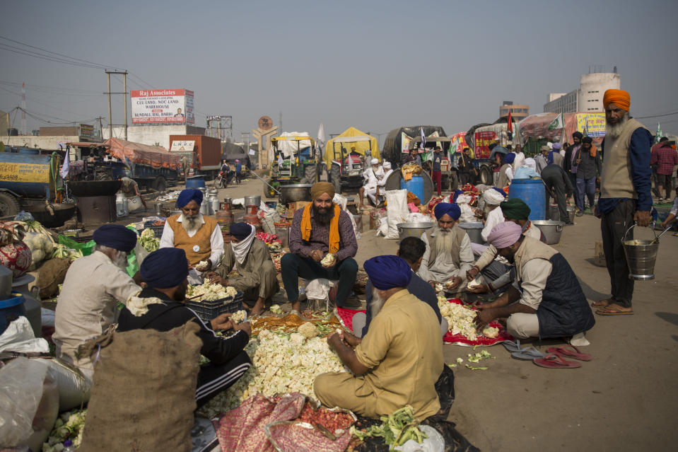 "Protesting farmers prepare a meal for fellow farmers as they block a major highway during a protest to abolish new farming laws they say will result in exploitation by corporations, eventually rendering them landless, at the Delhi-Haryana state border, India, Tuesday, Dec. 1, 2020. The busy, nonstop, arterial highways that connect most northern Indian towns to this city of 29 million people, now beat to the rhythm of never-heard-before cries of ""Inquilab Zindabad"" (""Long live the revolution""). Tens and thousands of farmers, with colorful distinctive turbans and long, flowing beards, have descended upon its borders where they commandeer wide swathes of roads. (AP Photo/Altaf Qadri)"