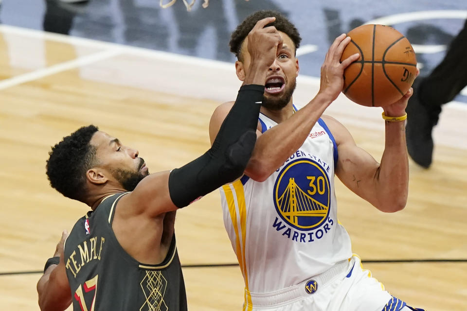 Golden State Warriors guard Stephen Curry, right, drives to the basket against Chicago Bulls guard Garrett Temple during the second half of an NBA basketball game in Chicago, Sunday, Dec. 27, 2020. (AP Photo/Nam Y. Huh)