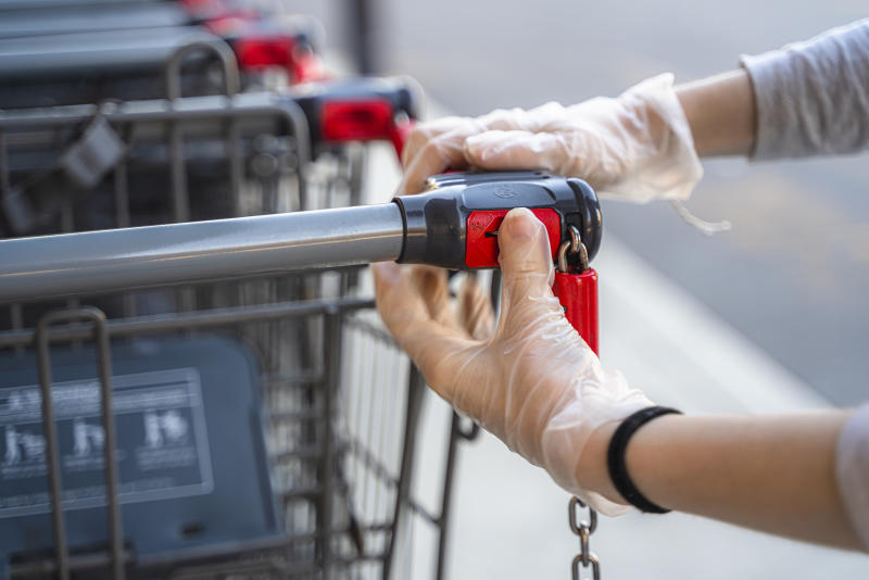 Close-up shot of the hands of a young woman wearing protective gloves taking a shopping cart in front of a grocery store to go and get groceries during the COVID-19