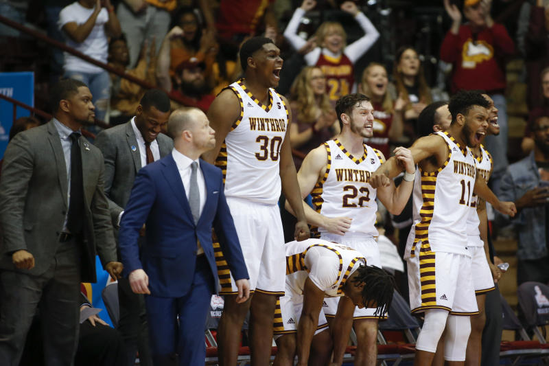The Winthrop bench celebrates in the second half of an NCAA college basketball game against Hampton for the Big South tournament championship in Rock Hill, S.C., Sunday, March 8, 2020. (AP Photo/Nell Redmond)