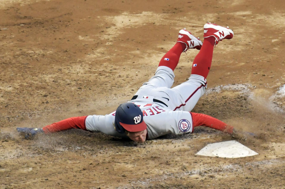 Washington Nationals' Andrew Stevenson scores on a sacrifice fly by Trea Turner during the 10th inning of the team's baseball game against the New York Yankees Saturday, May 8, 2021, at Yankee Stadium in New York. The Yankees won 4-3 in 11 innings. (AP Photo/Bill Kostroun)