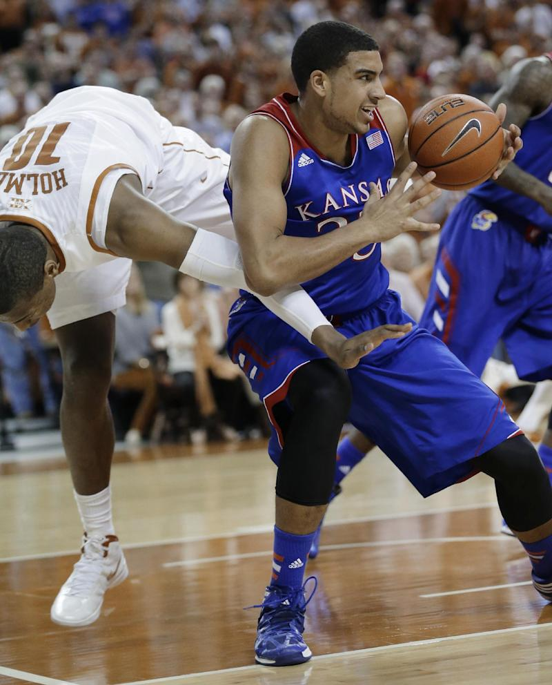 Texas' Jonathan Holmes (10) and Kansas' Landen Lucas, right, scramble for a loose ball during the first half of an NCAA college basketball game, Saturday, Feb. 1, 2014, in Austin, Texas. (AP Photo/Eric Gay)