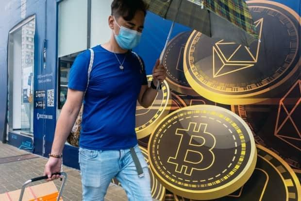 A pedestrian walks past signage for cryptocurrencies including ethereum bitcoin outside a cryptocurrency trader in the city. Beijing is cracking down on trading and mining of digital currencies. (Paul Yeung/Bloomberg - image credit)