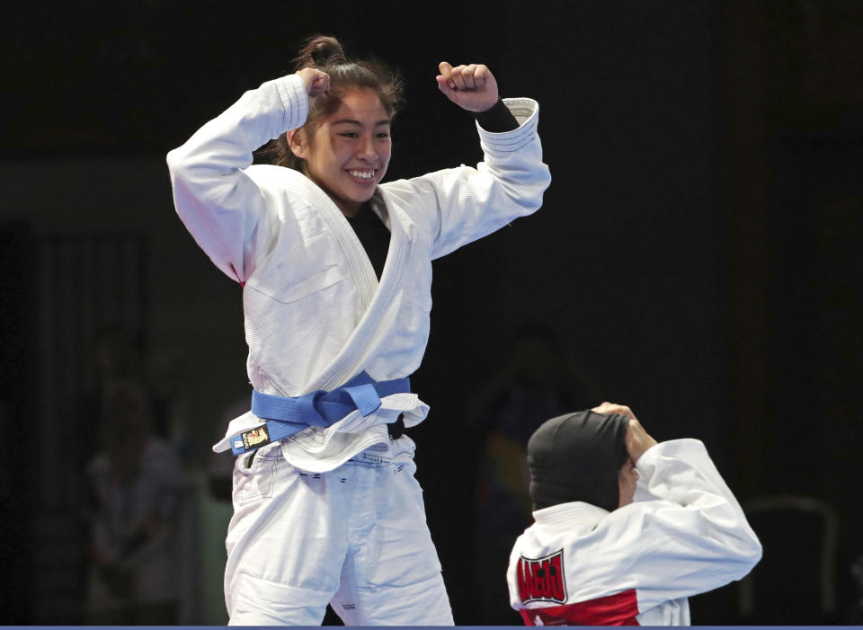 Jessa Khan of Cambodia, left, reacts after defeating Mahra Alhinaai of United Arab Emirates, right, during their newaza women's - 49 kilogram jujitsu final at the 18th Asian Games in Jakarta, Indonesia, Friday, Aug. 24, 2018. (AP Photo/Firdia Lisnawati)