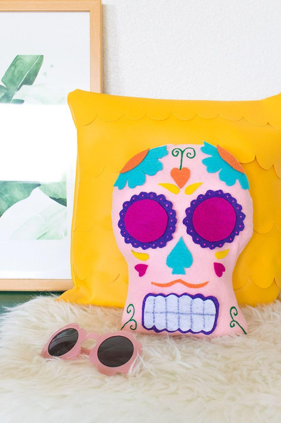 """<p>This DIY sugar skull pillow may look too beautiful and sophisticated to be an easy kids craft, but we assure you, it is! The """"face"""" is constructed almost entirely out of scraps of colorful felt. Cut out shapes for your kids (ages 8 and up will do best with this one), then let them construct the design with fabric glue.</p><p><strong>Get the tutorial at <a href=""""https://www.clubcrafted.com/2017/10/19/diy-dia-de-los-muertos-sugar-skull-pillow-a-video/"""" rel=""""nofollow noopener"""" target=""""_blank"""" data-ylk=""""slk:Club Crafted"""" class=""""link rapid-noclick-resp"""">Club Crafted</a></strong><strong>.</strong> </p>"""