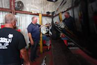 Bobby Ford (center) looks after the work being done on a truck in his shop, Bobby's Auto Service Center, on Wednesday, Sept. 1, 2021, in Vero Beach. Many of the employees at the shop became infected with COVID-19, including Ford's twin brother, Billy, who died Aug. 14 from the illness.
