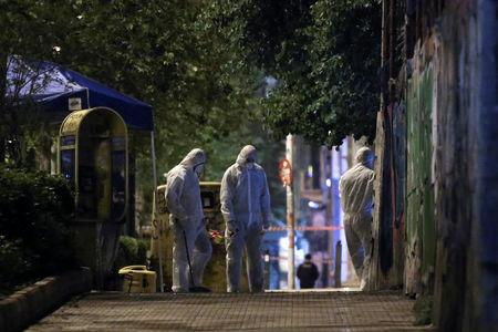 Forensics experts work at the scene after a bomb blast, in central Athens