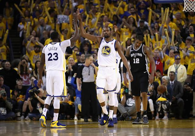 OAKLAND, CA - APRIL 24: Kevin Durant #35 high fives Draymond Green #23 of the Golden State Warriors after LaMarcus Aldridge #12 of the San Antonio Spurs turned the ball over in the final minutes of Game Five of Round One of the 2018 NBA Playoffs at ORACLE Arena on April 24, 2018 in Oakland, California. (Photo by Ezra Shaw/Getty Images)