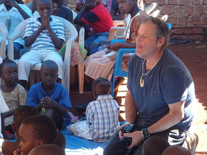 Mike Forster is seen here with several children in a village in Uganda, where he went on several annual missions to help poor children.