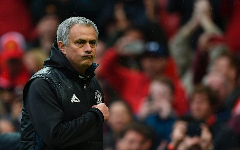 Manchester United's Portuguese manager Jose Mourinho points at the badge on his chest as he leaves the pitch - Credit: AFP