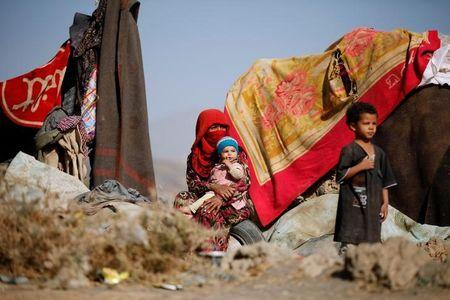 A woman sits with her children near their tent at a camp for internally displaced people in Dharawan, near the capital Sanaa
