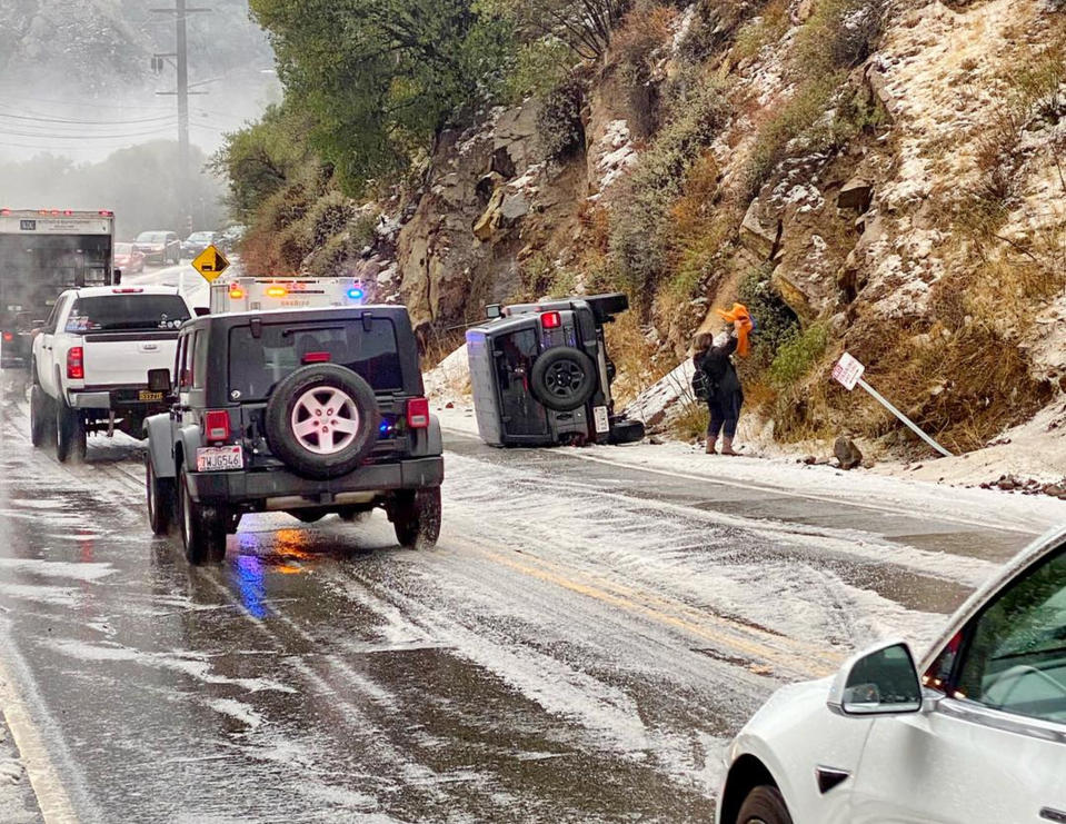 In this Saturday, Jan. 23, 2021, photo provided by the California Highway Patrol-West Valley, authorities work the scene of an accident after a hail storm on Malibu Canyon Road in Malibu, Calif. A hail storm struck the Santa Monica Mountains on Saturday, prompting the California Highway Patrol to warn drivers to slow down after officers responded to a few rollover accidents on Malibu Canyon. Up to a foot of snow fell in Southern California's mountains as the first in a series of storms move through California, bringing real winter weather after weeks of sporadic rain that has done little to ease drought. (California Highway Patrol via AP)