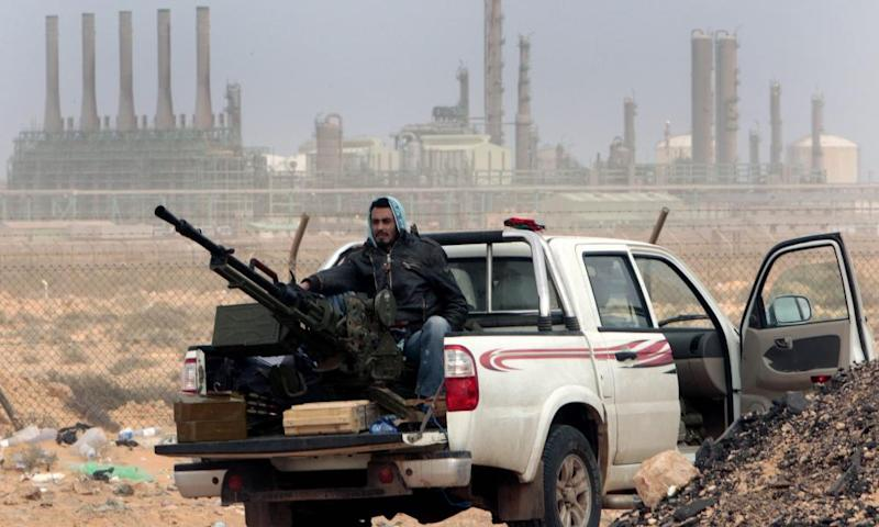 An anti-government rebel sits with an anti-aircraft weapon in front of an oil refinery in Ras Lanuf, eastern Libya.