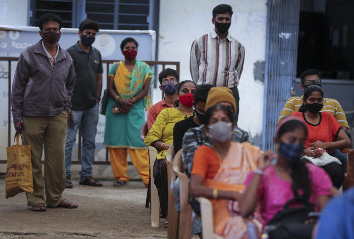 People wait to receive the vaccine for COVID-19 at a vaccination center set up at a government run school in Bengaluru, India, Tuesday, Sept. 21, 2021. India, the world's largest vaccine producer, will resume exports and donations of surplus coronavirus vaccines in October after halting them during a devastating surge in domestic infections in April, the health minister said Monday. (AP Photo/Aijaz Rahi)