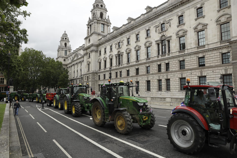 Farmers from the group Save British Farming drive tractors around Parliament Square, in London, in a protest against cheaply produced lower standard food being imported from the U.S. after Brexit that will undercut them, Wednesday, July 8, 2020. (AP Photo/Matt Dunham)