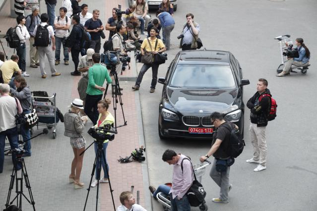 """Journalists stand next to Ecuador's Ambassador's car while waiting for the arrival of Edward Snowden, a former CIA employee who recently leaked top-secret documents about sweeping U.S. surveillance programs, at Sheremetyevo airport, just outside Moscow, Russia, Sunday, June 23, 2013. The former National Security Agency contractor, Snowdon is wanted by the United States for revealing two highly classified surveillance programs, but was allowed to leave Hong Kong for a """"third country"""" because a U.S. extradition request did not fully comply with Hong Kong law, the territory's government said Sunday. (AP Photo / Alexander Zemlianichenko Jr)"""