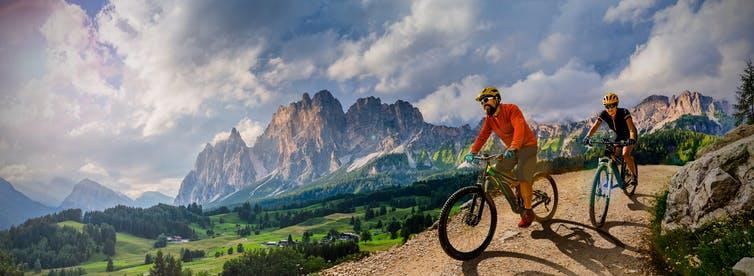Woman and Man riding on bikes in Dolomites mountains landscape.