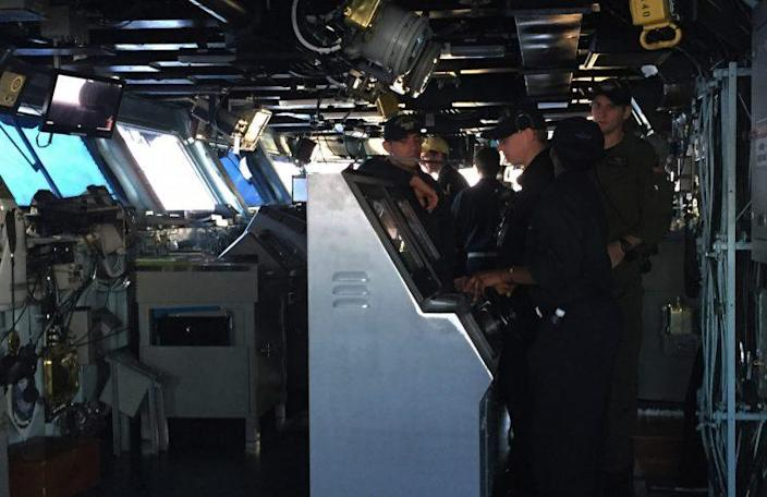 A Navy crew on the flight deck monitors arriving and departing flights.