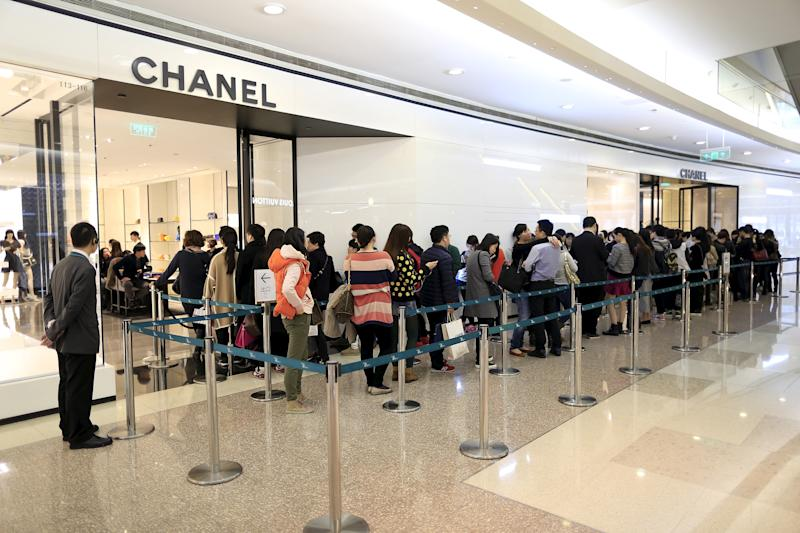 """Customers line up as they wait to go inside a Chanel shop at a shopping mall in Shanghai March 19, 2015. Global luxury brands expanding in China are better off targeting the HENRYs - """"high earners, not rich yet"""" - instead of the ultra-wealthy, as a slowing economy and a government that frowns on official excesses usher in an era of less showy spending. REUTERS/Aly Song"""