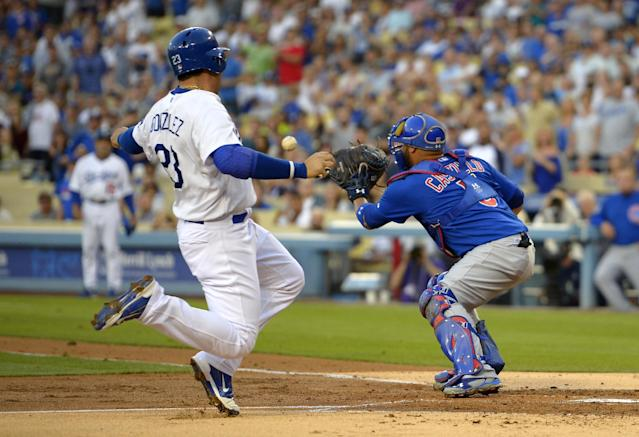 Los Angeles Dodgers' Adrian Gonzalez, left, starts to slide into home, before being tagged out by Chicago Cubs catcher Welington Castillo during the first inning of a baseball game, Friday, Aug. 1, 2014, in Los Angeles. (AP Photo/Mark J. Terrill)