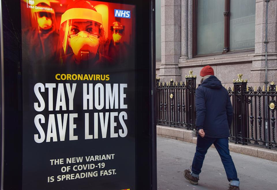LONDON, UNITED KINGDOM - 2021/01/09: A man walks past a 'Stay Home Save Lives' sign in Central London. The posters are part of a government campaign to get people to comply with lockdown rules as Coronavirus cases continue to rise. (Photo by Vuk Valcic/SOPA Images/LightRocket via Getty Images)