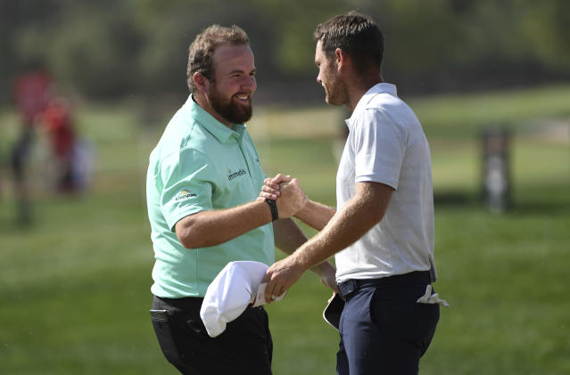 Shane Lowry, left, of Ireland shakes hands with Lucas Bjerregaard of Denmark after finishing at 10 under par on the 9th green in round one of the Abu Dhabi Championship golf tournament, in Abu Dhabi, United Arab Emirates, Wednesday, January 16, 2019. (AP/Martin Dokoupil)