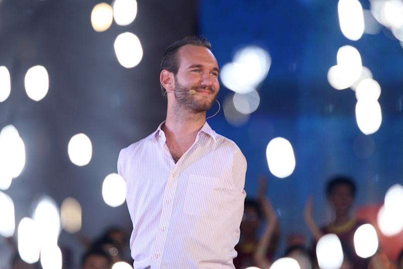 In this Thursday, May 23, 2013 photo, Nick Vujicic, a Serbian Australian evangelist who was born with no limbs, greets a crowd of about 25,000 students and young people at My Dinh national stadium in Hanoi, Vietnam. Vujicic, who is able to stand up and move around on his pelvis, shuffled round on a small table set up on a stage on corner of the field. In a talk laced with jokes, platitudes and attempts at Vietnamese, he spoke out against bullying and drinking; on the need for forgiveness and hope; and respect for family. All those themes resonate with Vietnamese and their leaders, one of whom - the vice president - was watching from the VIP area. (AP Photo/Na Son Nguyen)