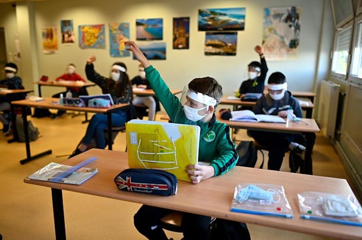 Schoolchildren wearing protective masks and face shields in a classroom at Claude Debussy college in Angers, France, on May 18 after France eased lockdown measures to curb the spread of the COVID-19.