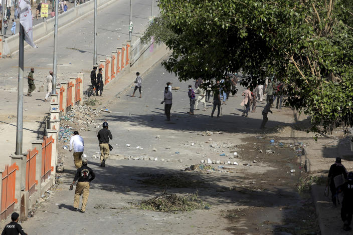 Police officers chase angry supporters of Tehreek-e-Labiak Pakistan, a radical Islamist political party, throwing stones during a clash following the arrest of their party leader Saad Rizvi, in Karachi, Pakistan, Tuesday, April 13, 2021. Two demonstrators and a policeman were killed Tuesday in violent clashes between Islamists and police in Pakistan, hours after authorities arrested Rizvi in the eastern city of Lahore, a senior official and local media reported. (AP Photo/Fareed Khan)