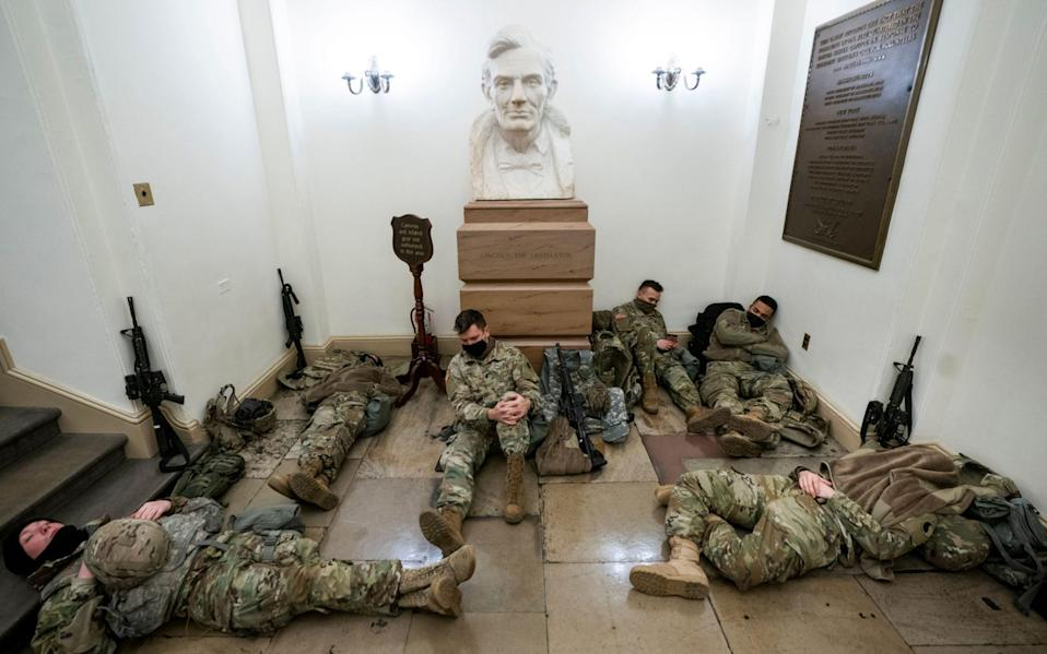 Members of the National Guard try to get some sleep inside the US Capitol in Washington - Shutterstock
