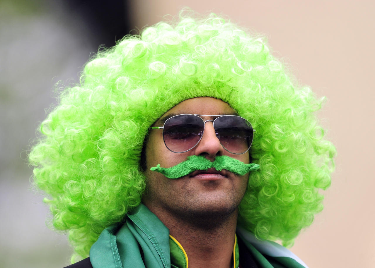 A cricket fan wears a green wig and moustache during the 2013 ICC Champions Trophy cricket match between Pakistan and India at Edgbaston in Birmingham, England on June 15, 2013. AFP PHOTO/GLYN KIRK