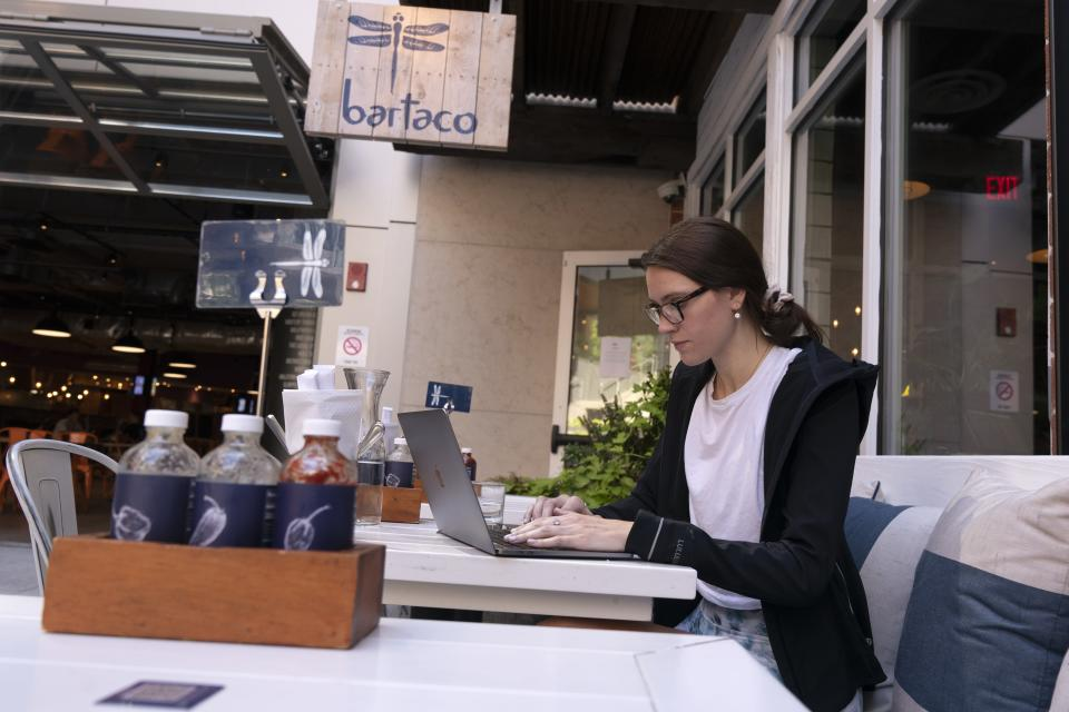 """Baylee Bowers works on her computer after ordering and paying for her meal using her cell phone at Bartaco in Arlington, Va., on Thursday, Sept. 2, 2021. The restaurant uses an automated app for ordering and payments. Instead of servers they use """"food runners"""" to get orders to tables. (AP Photo/Jacquelyn Martin)"""