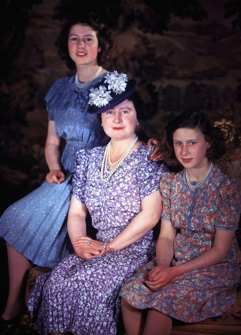 <p>A young Queen Elizabeth II and Princess Margaret pose with Queen Elizabeth the Queen Mother. The mother-daughter trio sport floral '40s-style dresses and matching pearls for the portrait.</p>