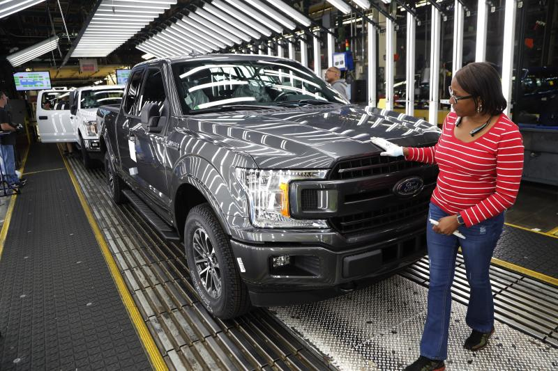 FILE- In this Sept. 27, 2018, file photo United Auto Workers' assemblyman Kelly Coman gives a final look to an assembled 2018 Ford F-150 truck on the assembly line at the Ford Rouge assembly plant in Dearborn, Mich. On Friday, Dec. 14, the Federal Reserve reports on U.S. industrial production for November. (AP Photo/Carlos Osorio, File)