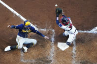 Milwaukee Brewers' Avisail Garcia (24) slides in to home as Atlanta Braves catcher Travis d'Arnaud (16) misses the tag during the fourth inning of Game 4 of a baseball National League Division Series, Tuesday, Oct. 12, 2021, in Atlanta. (AP Photo/John Bazemore)