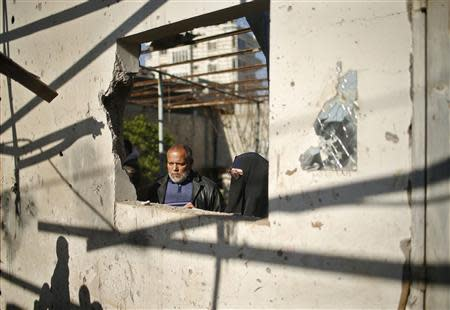 Palestinians inspect their house yard, which they said was hit in an Israeli air strike, in Gaza City
