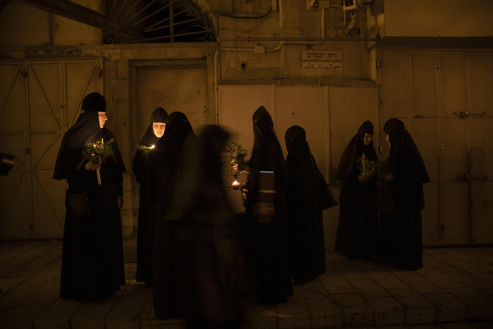 Orthodox nuns hold candles and flowers as they walk in a procession to bring the icon of the Virgin Mary to the tomb where it is believed she is buried, along the streets of Jerusalem's Old City, early Wednesday, Aug. 25, 2021. Every year before the Feast of the Assumption, the icon is brought from the Church of the Holy Sepulchre to the tomb of the Virgin Mary to honor her Assumption. (AP Photo/Oded Balilty)