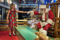 Sydney Poulos, 8, gives Santa a fist bump through a transparent barrier at a Bass Pro Shop in Bridgeport, Conn., Tuesday, Nov. 10, 2020. Santa Claus is coming to the mall — just don't try to sit on his lap. Malls are doing all they can to keep the jolly old man safe from the coronavirus, including banning kids from sitting on his knee, no matter if they've been naughty or nice. (AP Photo/Seth Wenig)