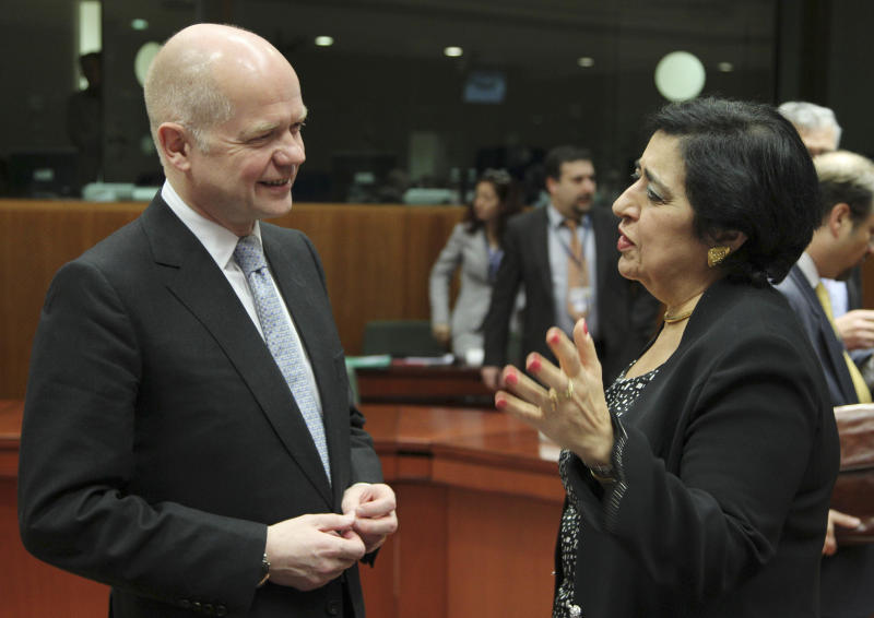 British Foreign Secretary William Hague, left, talks with Cypriot Foreign Minister Erato Kozakou-Markoullis, prior to the start of an EU Foreign Ministers council, at the European Council building in Brussels, Friday, March 23, 2012. Officials say that the EU foreign ministers have slapped sanctions on the wife and other close relatives of Syrian President Bashar Assad in a continuing attempt to stop the violent crackdown on opposition. They said four members of the Assad family and eight government ministers have been targeted in the latest round of sanctions. (AP Photo/Yves Logghe)