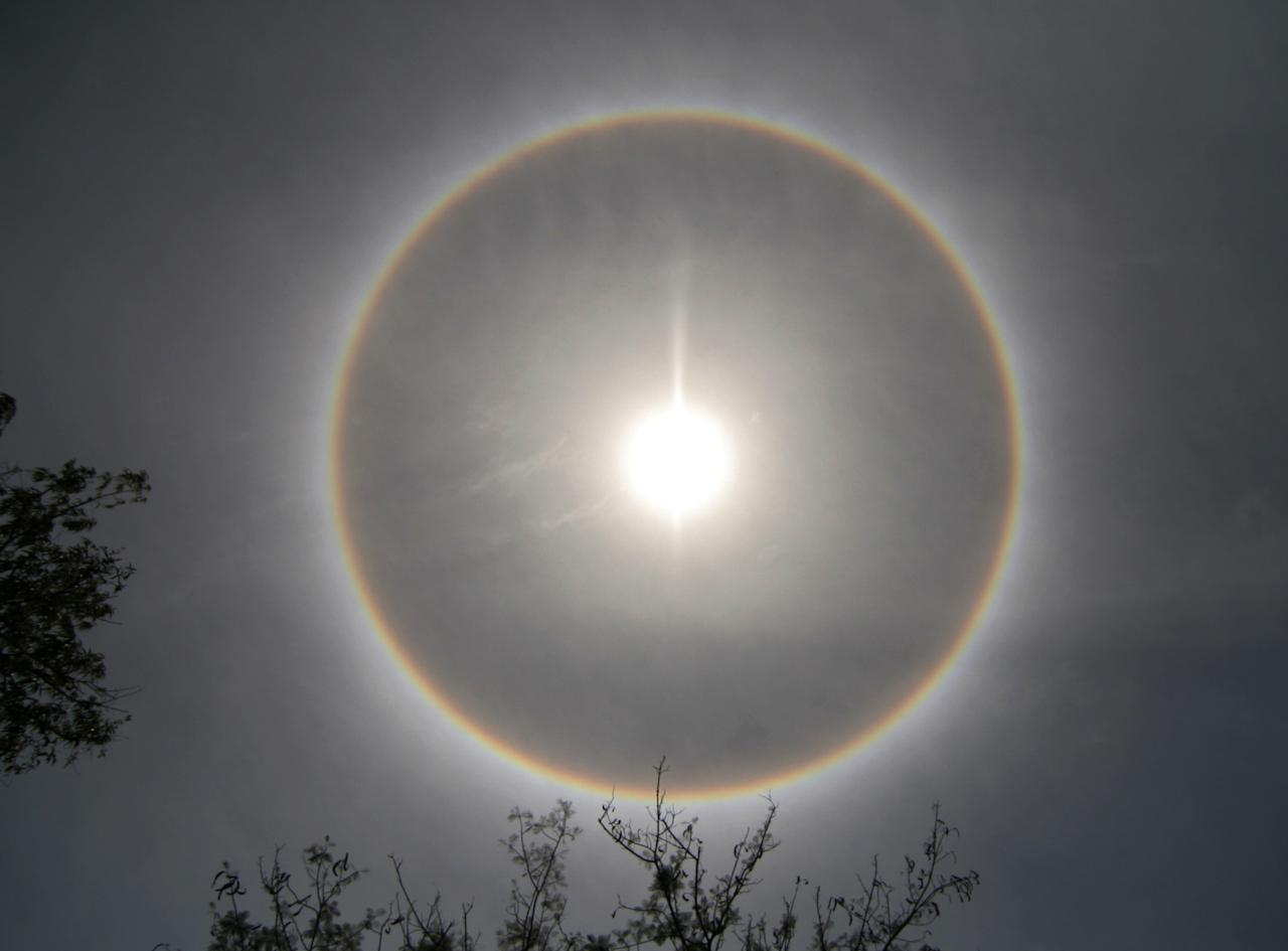 A halo, an optical phenomenon that appears around the Sun, is photographed in Medan in Indonesia's North Sumatra province September 22, 2008. REUTERS/Y.T. Haryono   (INDONESIA) - RTX8SUD