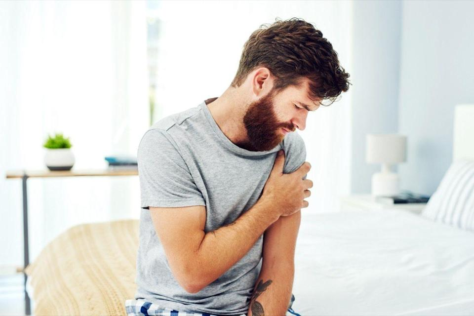 A man experiencing discomfort in his upper arm
