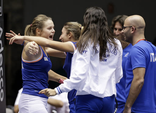 Italy's Karin Knapp, left, is mobbed by teammates after defeating United States' Alison Riske 6-3, 7-5, during a Fed Cup world group tennis match on Sunday, Feb. 9, 2014, in Cleveland. (AP Photo/Tony Dejak)
