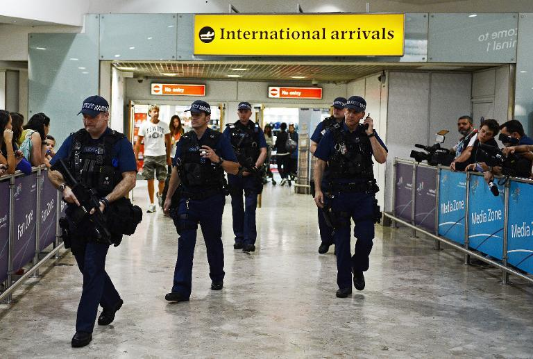 Armed police officers walk in front of the arrival gate at Heathrow airport in London, on July 23, 2012 (AFP Photo/Carl de Souza)