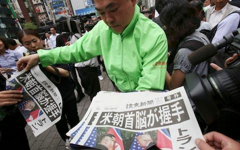 <span>A staff of a Japanese news paper Yomiuri distributes an extra edition of the newspaper reporting the summit</span> <span>Credit: Koji Sasahara/AP </span>