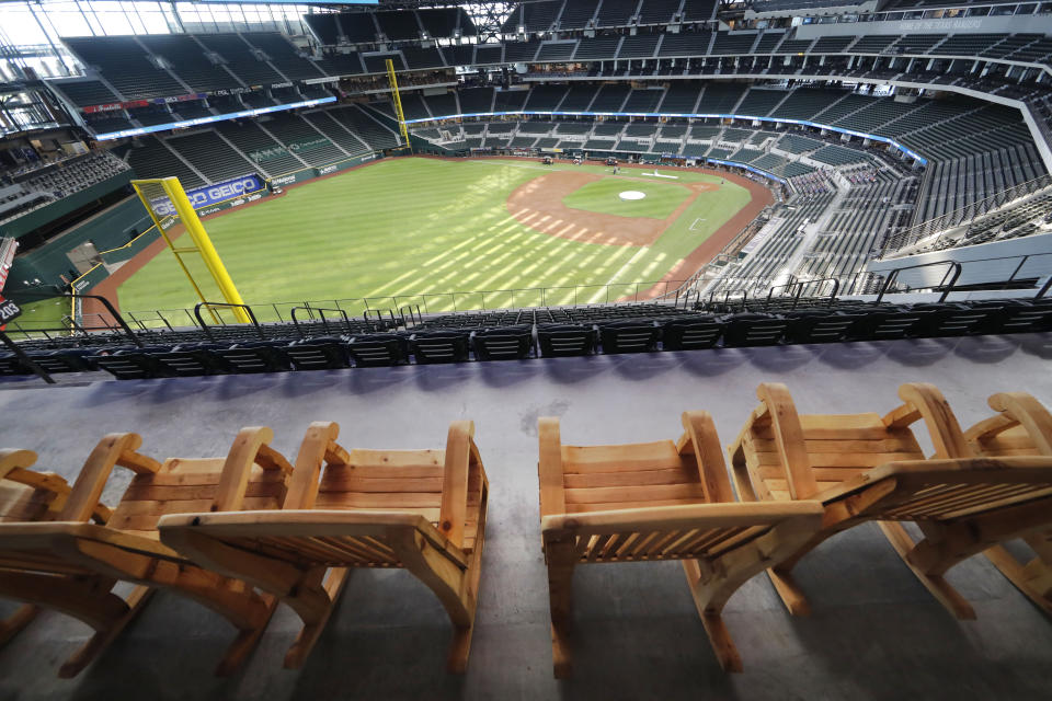 FILE - In this Thursday, July 23, 2020, file photo, oversized rocking chairs sit ready for fans on the patio at the Texas Rangers home baseball stadium, Globe Life Field, in Arlington, Texas. The Texas Rangers could have a full house for their home opener next month after debuting their new 40,518-seat stadium without fans in the stands for their games last season. If that happens, the Rangers could be the first team in MLB or any U.S.-based sport to have a full-capacity crowd since the coronavirus pandemic started rapidly shutting down sports a year ago this week. (AP Photo/LM Otero, File)