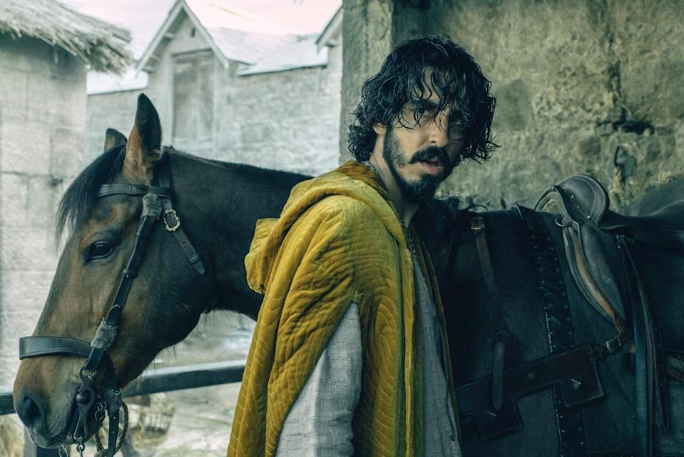 Dev Patel stands by a horse