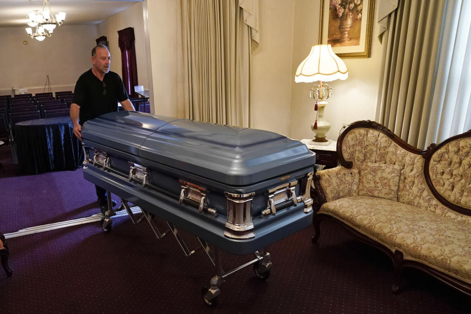 FILE - In this Tuesday, Aug. 10, 2021 file photo, Callahan Funeral Home director Ellis McAninich moves a casket for display to a room in the home in Callahan, Fla. McAninich has overseen funerals for five people who died from the virus since July he himself has recovered from a bout with the virus and now plans to get vaccinated. On Friday, Aug. 26, 2021, The Associated Press reported on stories circulating online incorrectly asserting that COVID-19 vaccines are more deadly than the virus itself. In fact, reports of death resulting from COVID-19 vaccination are rare while more than 4 million people worldwide have died from COVID-19. (AP Photo/John Raoux, File)