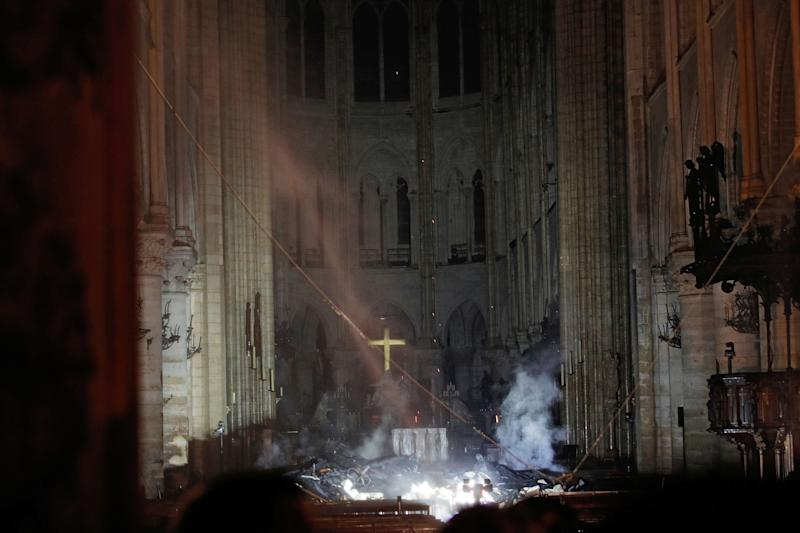 Smoke rises around the altar in front of the cross inside the Notre Dame Cathedral (Picture: Reuters)