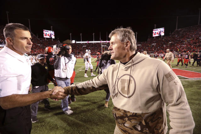 Utah head coach Kyle Whittingham, right, shakes hands with Oregon head coach Mario Cristobal following their NCAA college football game Saturday Nov. 10, 2018, in Salt Lake City. (AP Photo/Rick Bowmer)